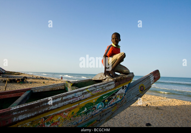 Boy on a Boat on the Beach in St Louis in Senegal West Africa - Stock Image