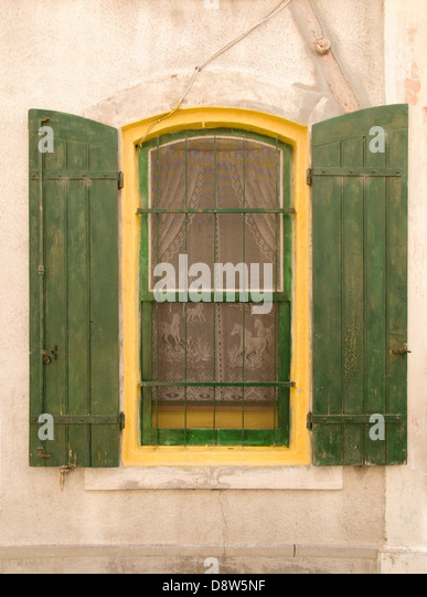 A window with bars and open shutters on a house in Arles, France - Stock Image