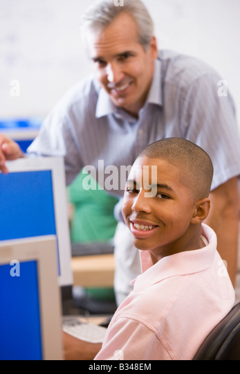 Teacher with male student in computer class - Stock Image