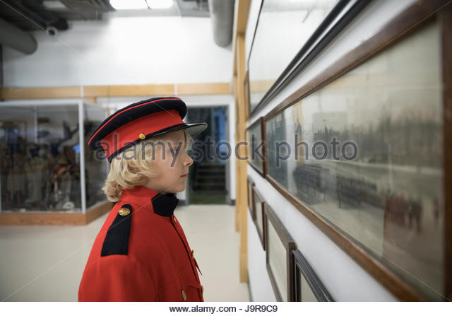Curious boy student wearing military uniform, looking at photograph exhibit on field trip in war museum - Stock-Bilder