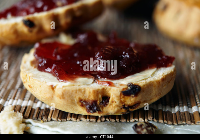 Close up of sliced scone with jam - Stock Image