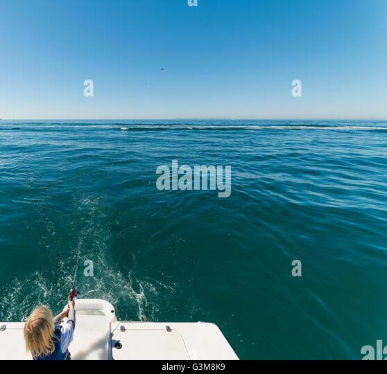 Boy fishing on sailboat - Stock Image