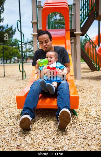 Young man with toddler brother on playground slide - Stock Image
