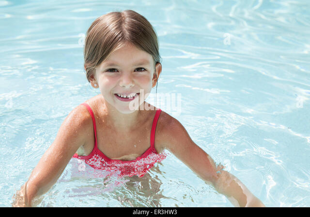 Girl swimming in pool, portrait - Stock Image