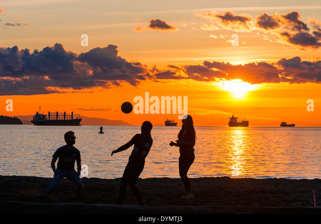A game of beach volleyball at sunset, English Bay Beach, Vancouver, British Columbia, Canada - Stock Image
