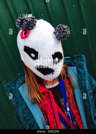 Child wearing knitted panda mask. - Stock Image