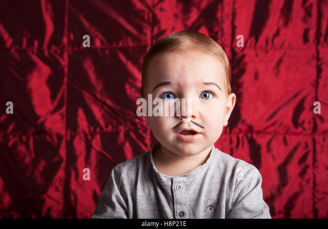Portrait of a little boy dress up for halloween party. Red satin background - Stock Image