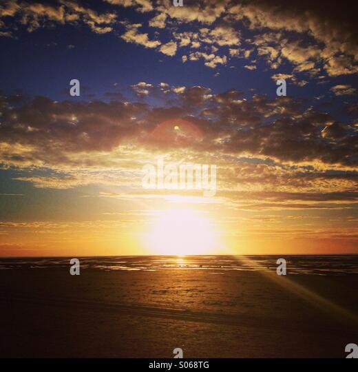 Sun setting over Liverpool Bay, England. - Stock Image