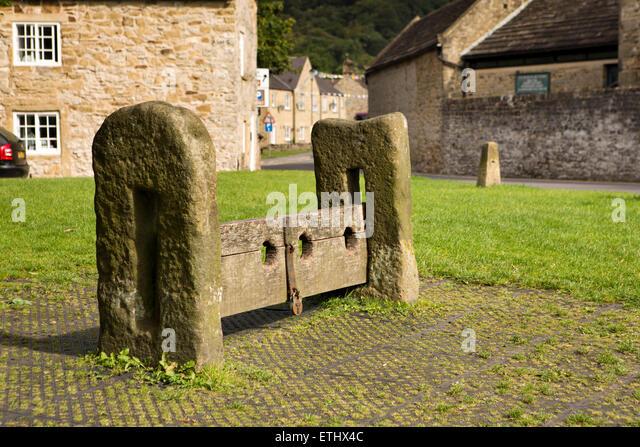 UK, England, Derbyshire, Eyam, Market Square, early C19th stone an wooden punishment stocks - Stock Image