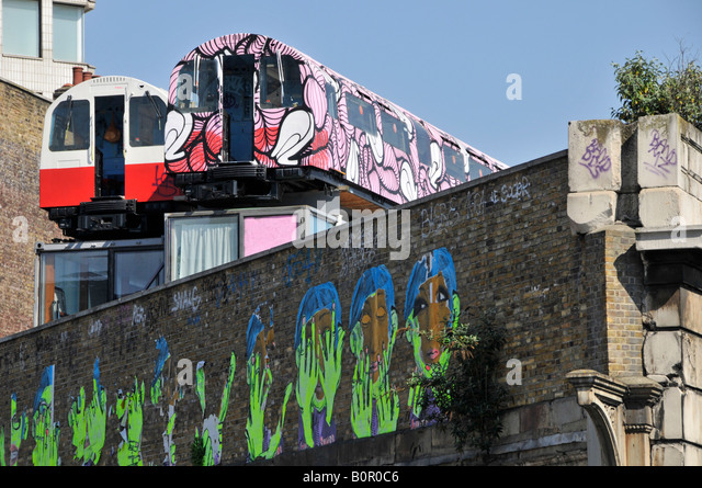 Recycled tube train carriages used as artists studios above old railway viaduct with walls used for arty graffiti - Stock Image
