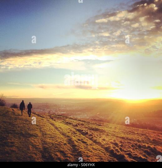 Distant walkers taking a Sunday late afternoon stroll as the sun casts rays over the outskirts of the City of Bath - Stock Image