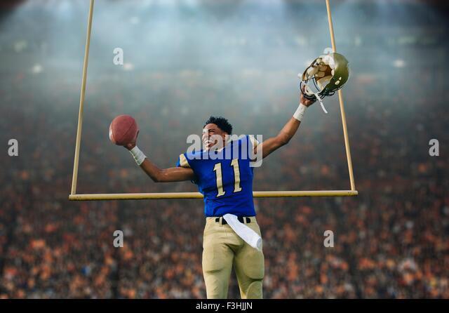 Teenage American football player celebrating victory in soccer stadium - Stock Image
