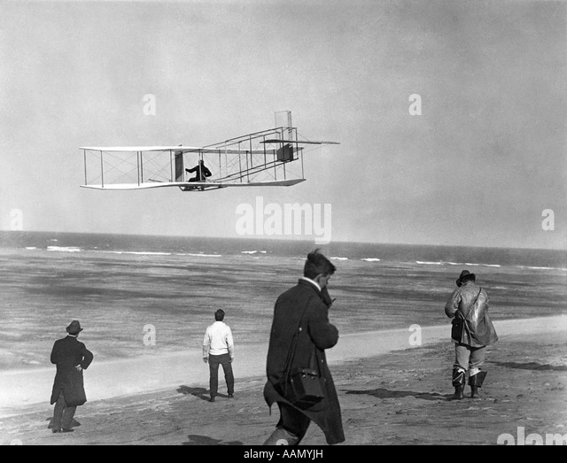 ONE OF THE WRIGHT BROTHERS FLYING GLIDER BY THE OCEAN AND SPECTATORS ON BEACH BELOW KITTY HAWK NORTH CAROLINA USA - Stock Image