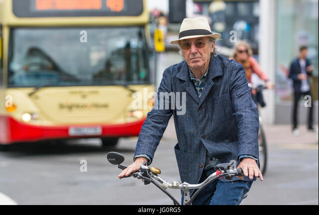 Stylish suave looking middle aged to older man in a summer hat and denim outfit cycling on a busy road. - Stock Image