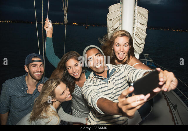 Friends on sailing boat photographing themselves - Stock Image