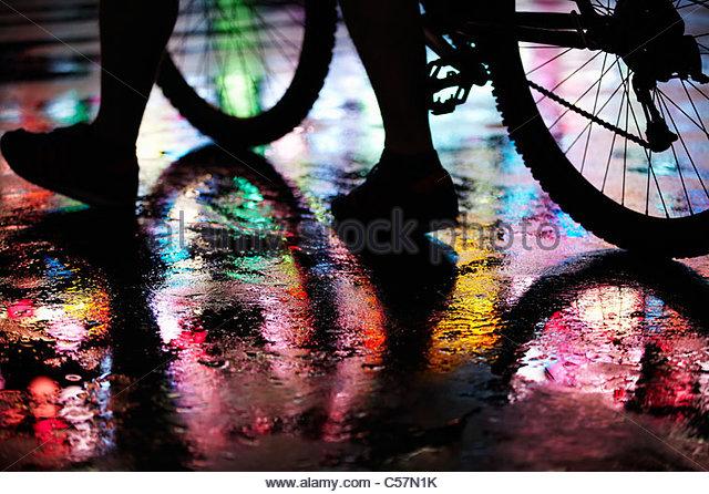 Wet city street lit by neon lights - Stock Image