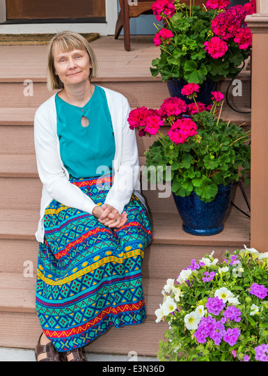 Portrait of middle-aged woman seated outside on front porch with potted flowers - Stock Image