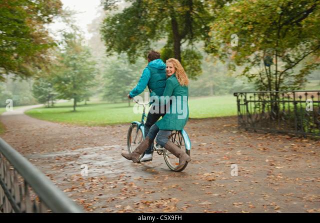 Germany, Bavaria, Munich, English Garden, Couple riding bicycle - Stock Image