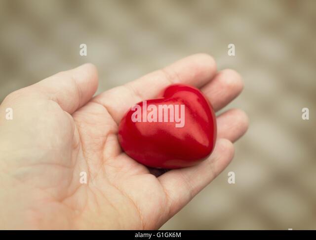Young woman holds out a red heart in her hand, concept of love, kindness and empathy - Stock Image