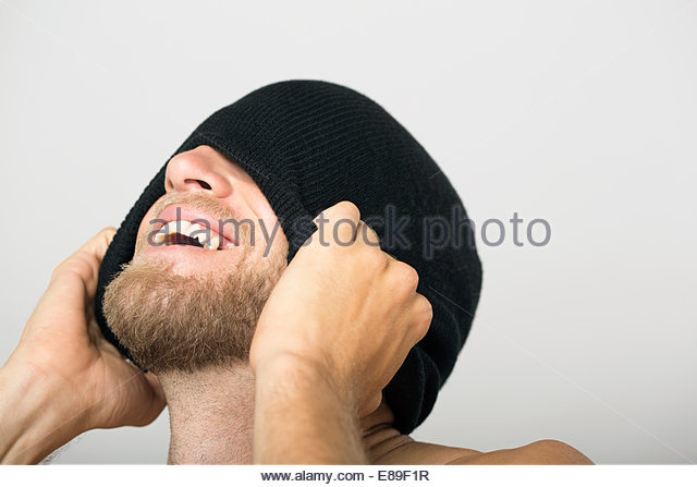 Laughing bearded man covering face with stocking-cap - Stock Image