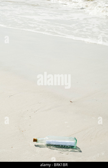 Message in a bottle washed up on beach - Stock Image