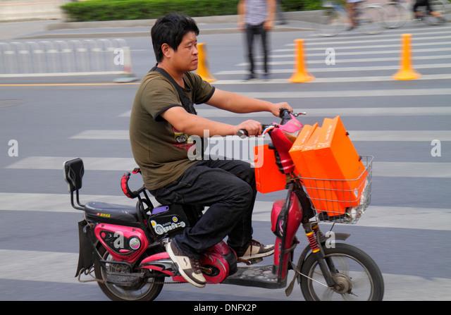 China Beijing Guang An Men Nei Da Jie Guanganmen Outer Street Asian man electric motor scooter riding - Stock Image