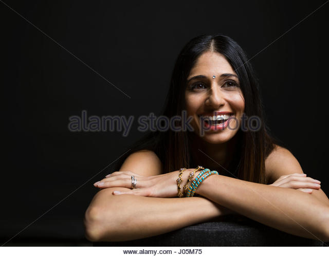 Portrait laughing Indian woman with bindi against black background - Stock Image