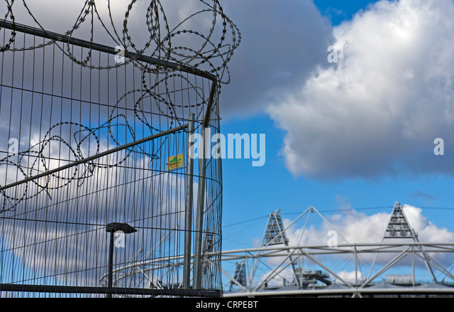 Razor wire security fencing in front of the London Olympic Stadium. - Stock Image