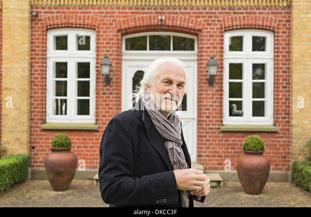 Portrait of senior man wearing jacket and scarf outside house - Stock Image