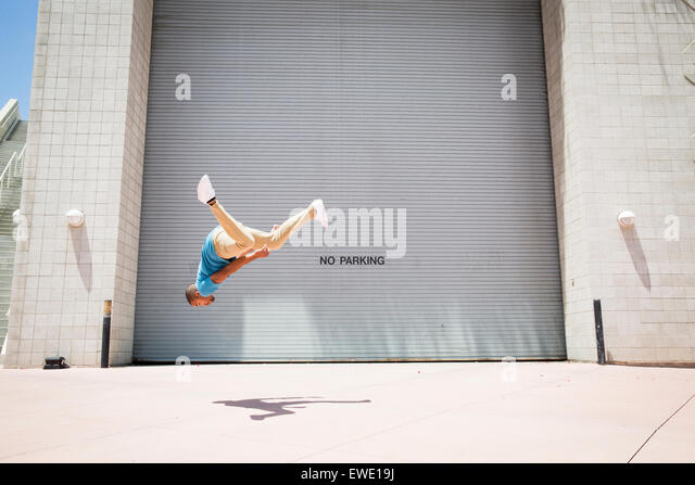Young man somersaulting on street parcour parkour free running - Stock Image
