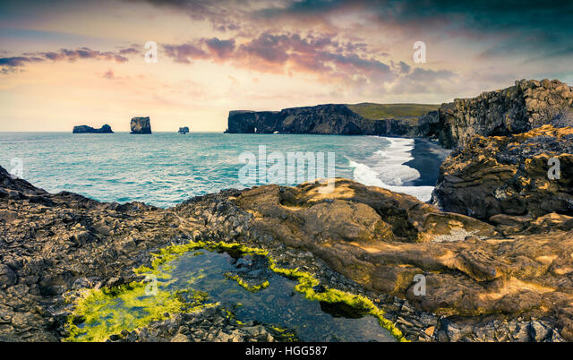 Colorful summer sunset in Dyrholaey Nature Reserv. Dramatic view of Dyrholaey arch, south coast of Iceland, Europe. - Stock Image