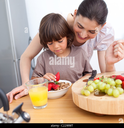 Jolly mother and her child having breakfast - Stock Image