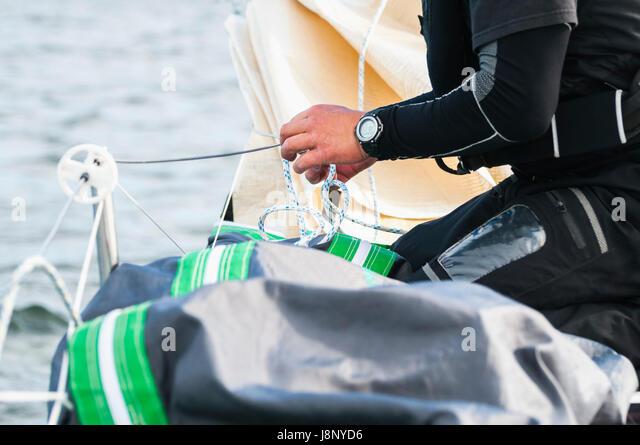 Man holding string by water - Stock-Bilder