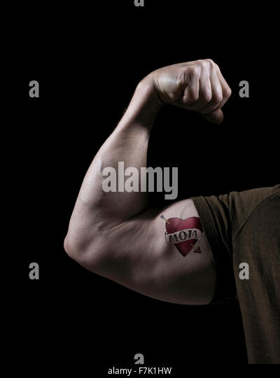 Studio shot of a muscular arm with mom tattoo - Stock Image