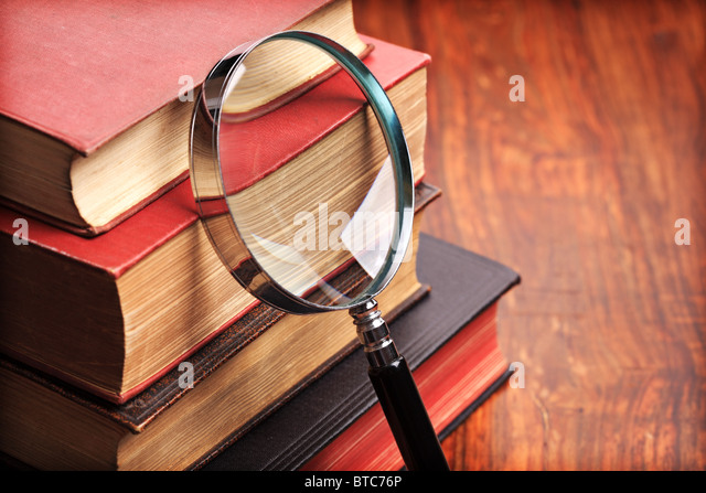 Magnifying glass with old books - Stock Image