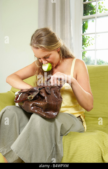Young woman searching in handbag - Stock Image