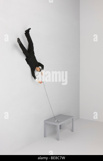 Businessman floating upside down holding landline phone, cutting cord with scissors - Stock Image