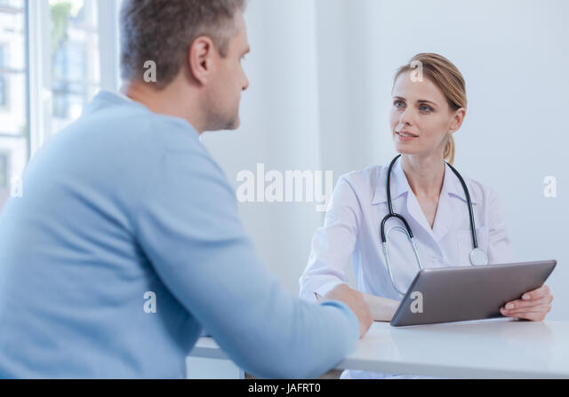 Full of empathy. Stylish involved positive physician enjoying appointment and using tablet while expressing joy - Stock Image