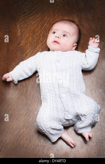 1 - 2 months baby boy lying on wooden floor - Stock Image