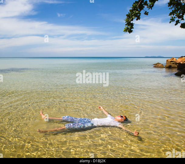 paradise beach, tourist relaxing in transparent water - Stock Image