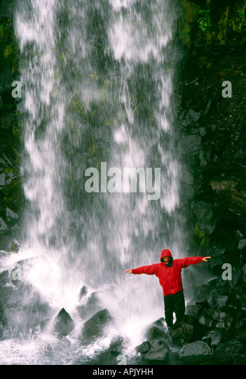 PICTURE CREDIT DOUG BLANE Carl Galvin in a red Mountain Equipment gore tex jacket under Svartifoss Waterfall in - Stock Image