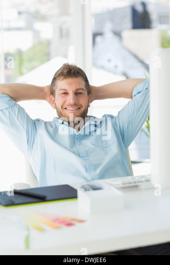 Handsome designer relaxing at his desk smiling at camera - Stock Image