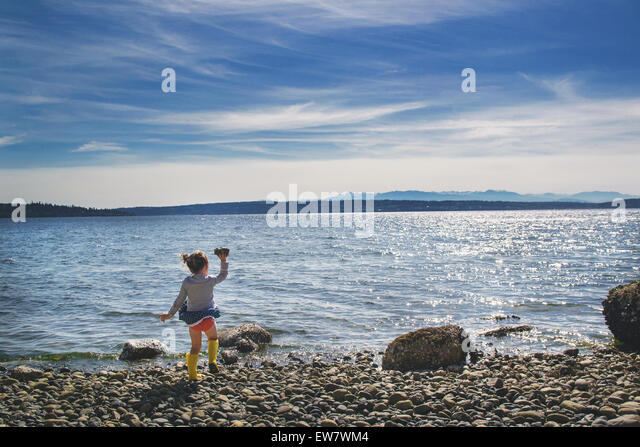 Girl throwing a rock into the sea on a windy day - Stock Image