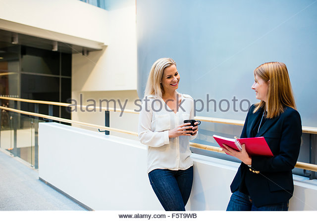 Finland, Two women talking in office corridor - Stock Image