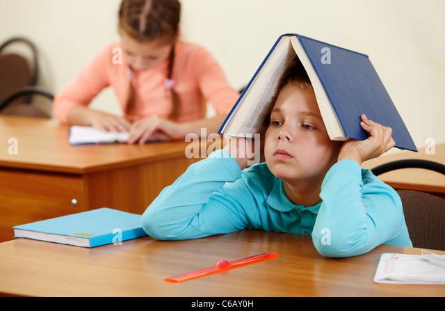 Cute schoolboy keeping open book on head in classroom - Stock Image