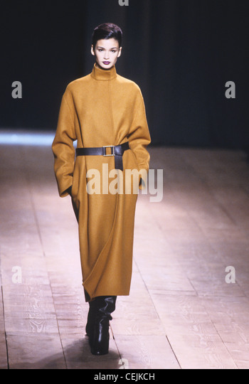 Yves Saint Laurent Autumn Winter Oversize long brown coat with black leather belt, and black slouchy knee length - Stock Image