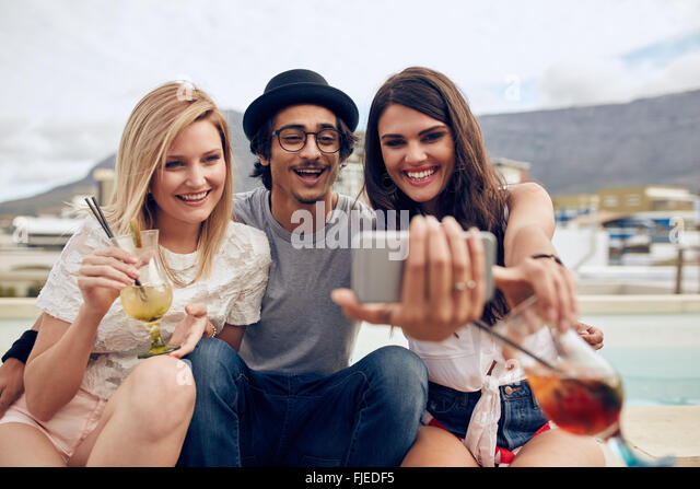 Group of friends taking selfie on a smart phone. Young man and women with drinks taking a self portrait on cell - Stock Image