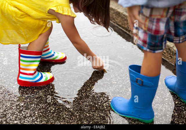 Boy and sister wearing rubber boots looking down at in rain puddle - Stock-Bilder