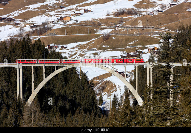 Red train of Rhaetian Railway on Langwieser Viaduct surrounded by woods, Canton of Graubunden, Switzerland - Stock-Bilder
