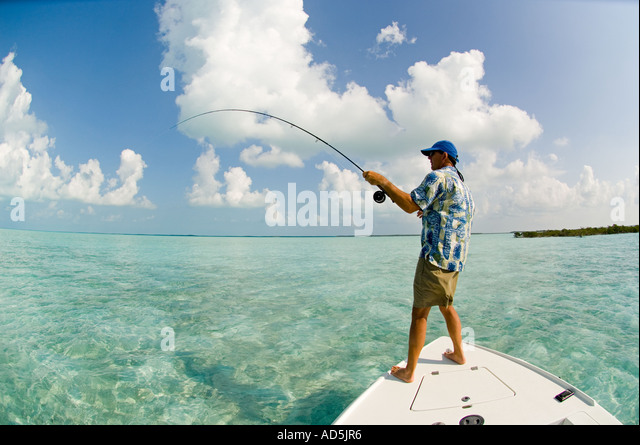 GREATER EXUMA  BAHAMAS Fisherman fighting Bonefish on fly rod from fishing boat in emerald green waters Atlantic - Stock Image